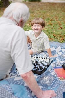 Un grand-père enseigne les petits échecs