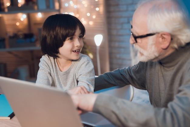 Grand-père expliquer quelque chose à petit-fils avec un ordinateur portable