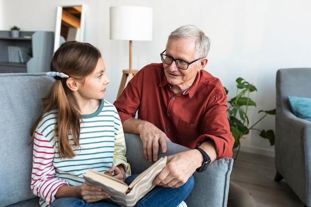 Grand-père et fille tenant un livre