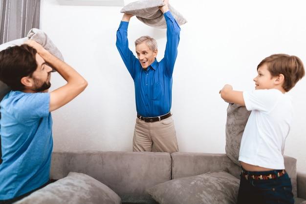 Grand-père, fils adulte et petit-fils se battent avec des oreillers.