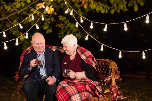 Grand-père et grand-mère boivent du thé dans le parc.