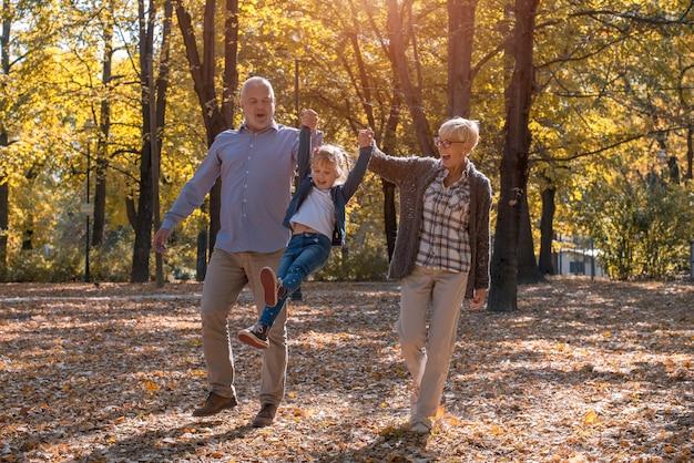 Grand-père et grand-mère jouant avec leur petit-fils dans un parc
