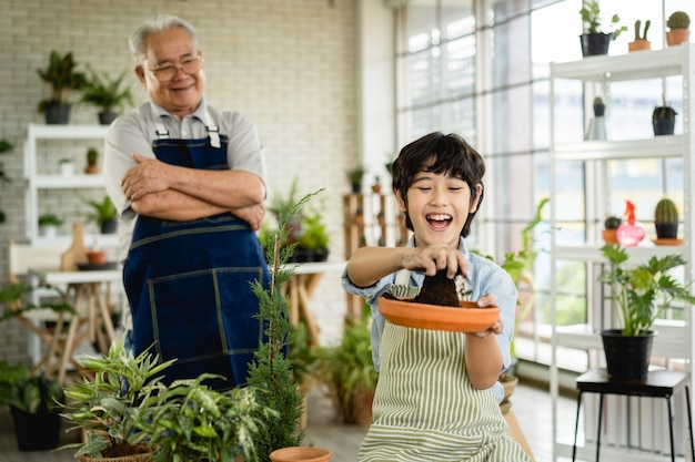 Grand-père jardinage et enseignement petit-fils prendre soin de l'usine