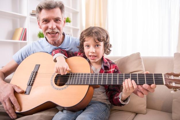 Grand-père joue de la guitare avec son petit-fils.