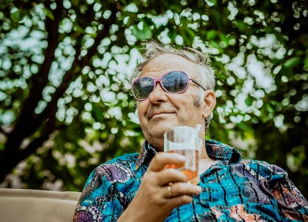 Grand-père moderne aime la vie avec un verre de boisson à la main