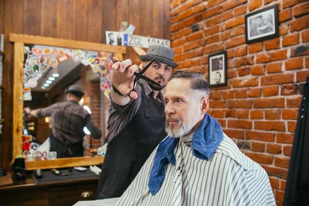 Grand-père obtient un coiffeur coupe de cheveux dans un salon de coiffure