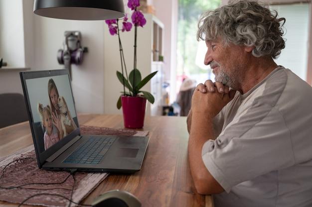 Grand-père parlant à sa famille - fille et petite-fille, via une réunion en ligne à l'aide d'un ordinateur portable.