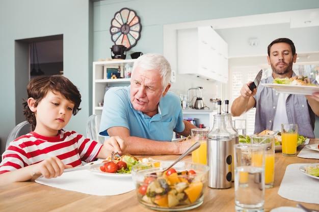 Grand-père parle à son petit-fils assis à la table