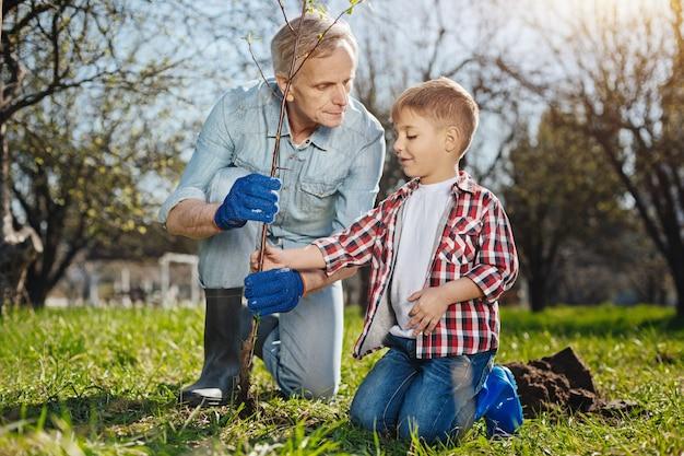 Grand-père passe du temps à l'extérieur avec son petit-fils, à la fois souriant et appréciant le processus