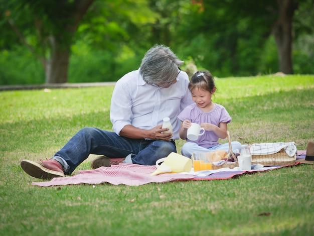 Le grand-père passe le temps en vacances avec ses petits-enfants au parc naturel.