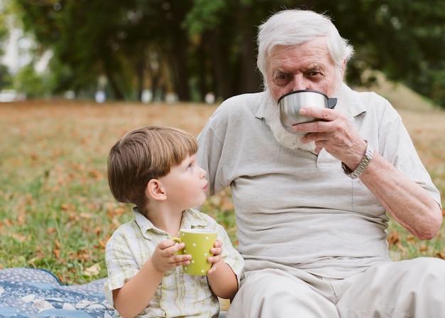 Grand-père et petit-fils dans un parc buvant du thé
