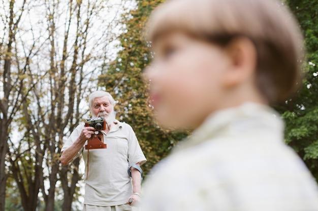 Grand-père avec petit-fils dans le parc en prenant des photos