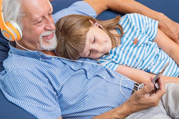Grand-père et petit-fils avec des écouteurs écoutent de la musique s'embrassant sur le canapé