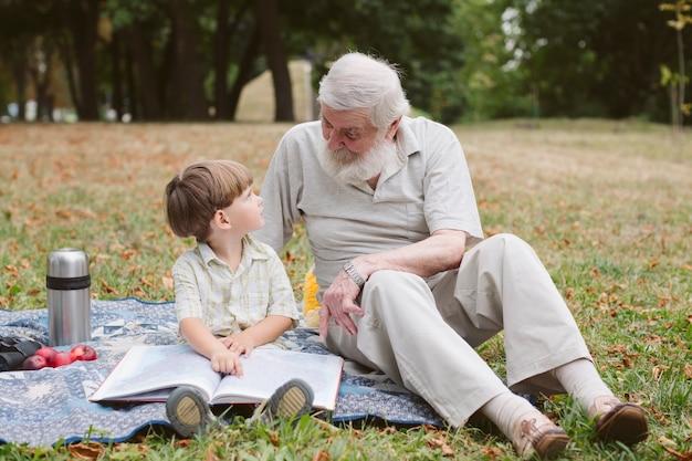 Grand-père et petit-fils lisant un pique-nique