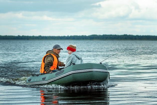 Grand-père et petit-fils montent en bateau à moteur sur le lac.