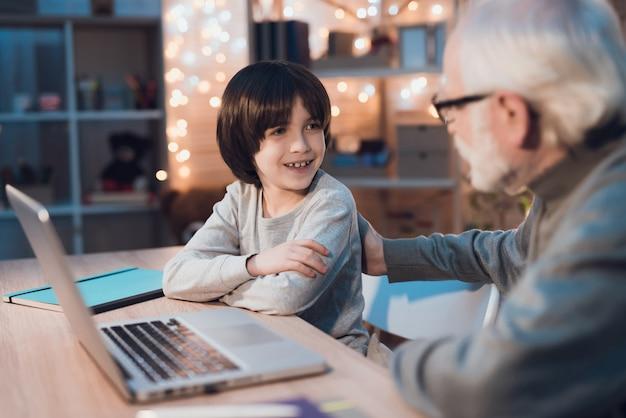 Grand-père et petit-fils parlant et utilisant un ordinateur portable