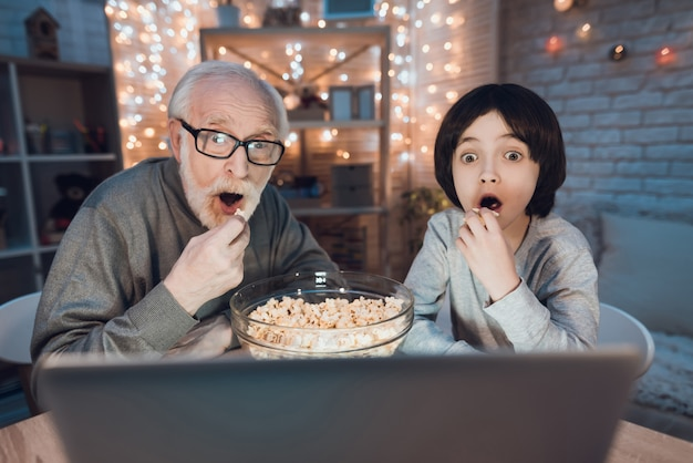 Grand-père petit-fils regardant un film effrayant sur un ordinateur portable