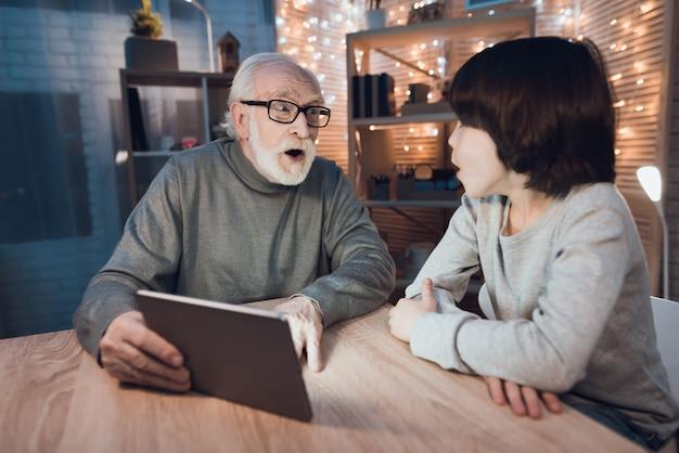Grand-père petit-fils regardant un film effrayant sur une tablette