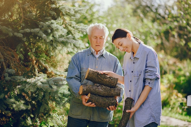 Grand-père avec petite-fille dans une cour avec du bois de chauffage dans les mains