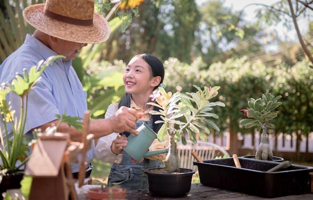 Grand-père et petite-fille plantant un arbre dans le jardin à la maison. mode de vie à l'âge de la retraite en famille pendant les vacances d'été.