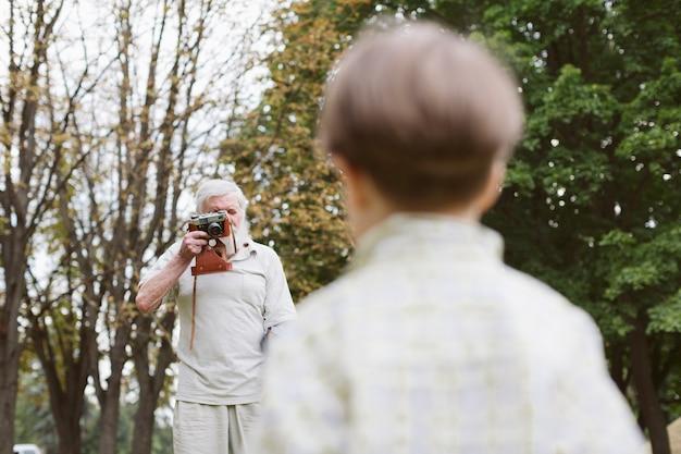 Grand-père prend des photos de petit-fils