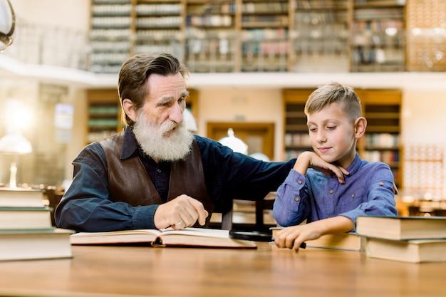 Grand-père son petit-fils, enseignant et étudiant, assis à la table dans l'ancienne bibliothèque