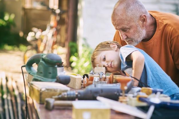 Grand-père et son petit-fils s'amusent dans l'atelier en plein air