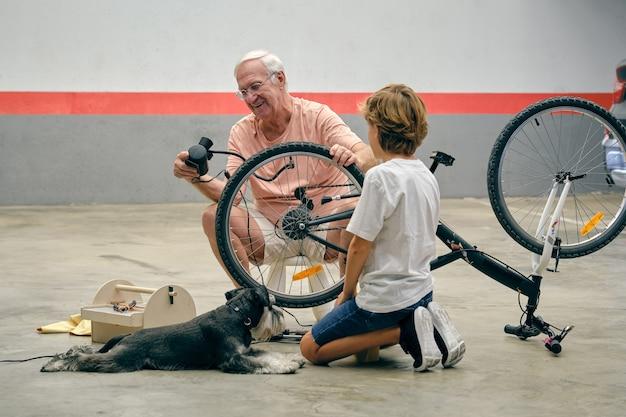 Grand-père souriant gonflant la roue de vélo avec petit-fils et chien