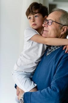 Grand-père tenant son petit-fils près de la fenêtre