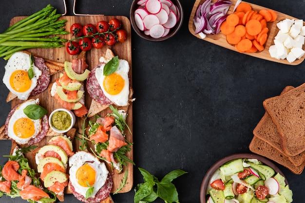 Grand petit-déjeuner sain avec des sandwiches avec des œufs brouillés, des saucisses, du saumon, de la roquette, du fromage blanc, de l'avocat sur une planche de bois
