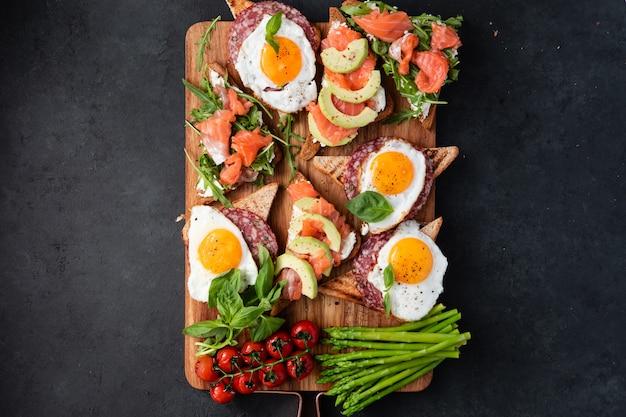 Grand petit-déjeuner sain avec des sandwiches avec des œufs brouillés, des saucisses, du saumon, de la roquette, du fromage blanc, de l'avocat