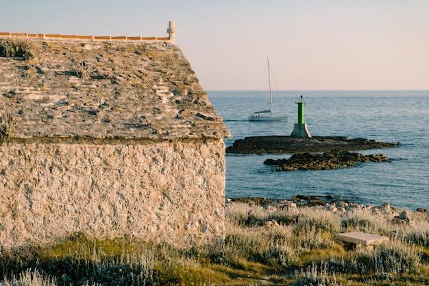 Un grand phare vert en métal sur un rocher dans la mer près du cap punta planka en croatie