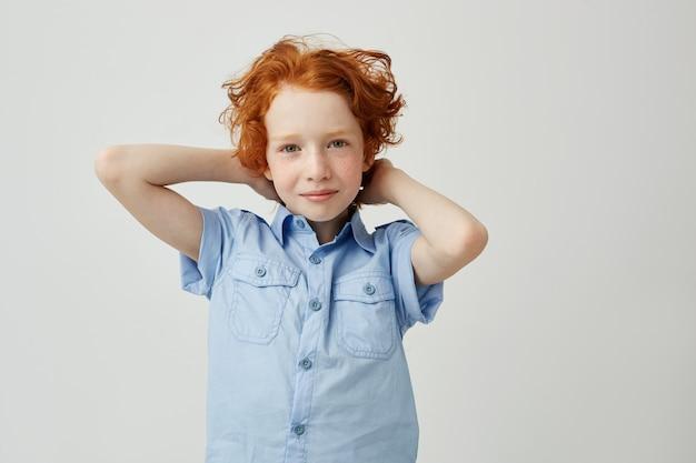 Grand plan, de, beau, gingembre, gosse, à, cheveux urly, et, taches rousseur, dans, chemise bleue, tenant mains, tête