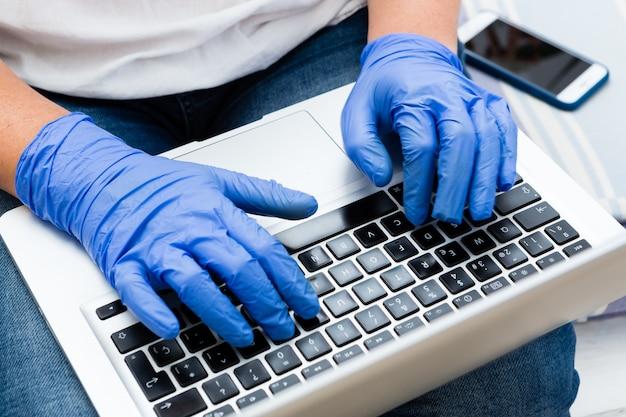 Grand plan, maison travail, femme, dactylographie, sur, ordinateur portable, à, gants chirurgicaux