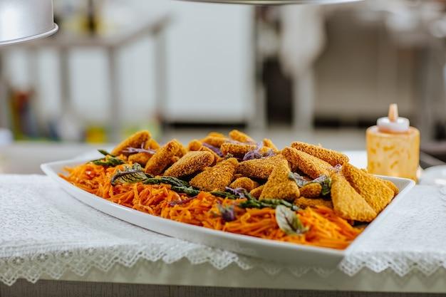 Grand plat avec des collations de poulet et carottes