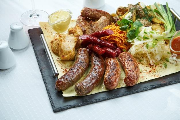 Grand plat avec saucisses grillées, saucisses fumées, brochettes de poulet et de porc avec accompagnements de pommes de terre au four et chou.
