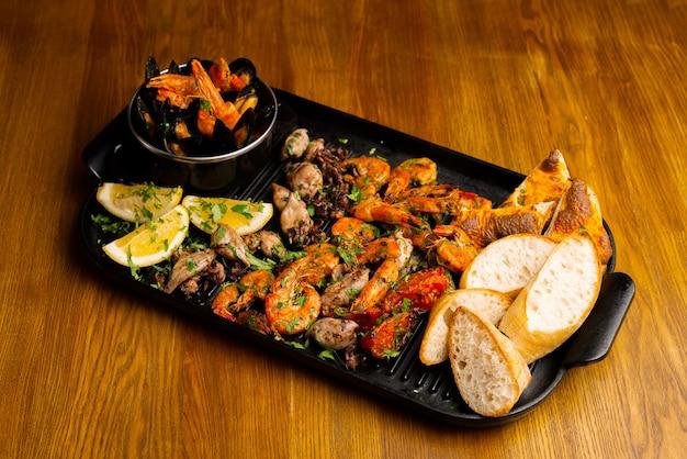 Grand plateau noir avec de délicieux fruits de mer sur table en bois.