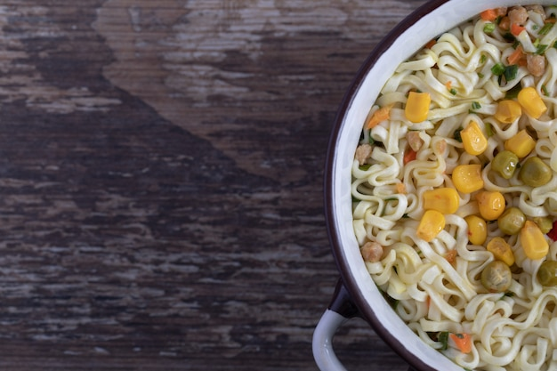 Un grand pot de nouilles savoureuses avec des légumes sur fond de marbre