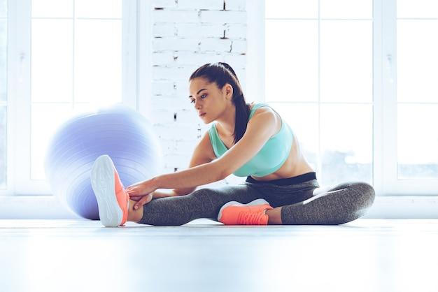 Grand progrès. belle jeune femme en vêtements de sport faisant des étirements assis sur le sol devant la fenêtre de la salle de sport