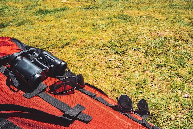 Grand sac à dos de camping rouge avec des articles de voyageur (lunettes de soleil, jumelles) sur l'herbe en journée ensoleillée.
