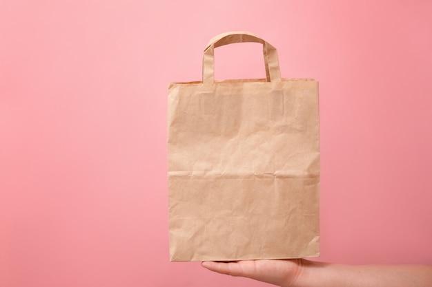 Grand sac en papier dans une main féminine sur un rose