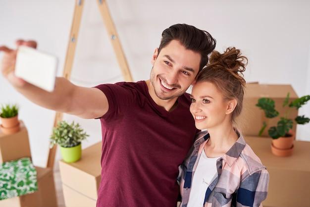 Grand selfie de couple souriant dans leur nouvelle maison