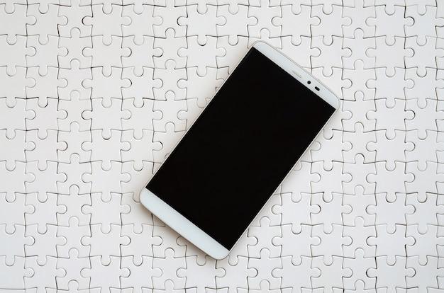 Un grand smartphone moderne doté d'un écran tactile repose sur un puzzle blanc assemblé