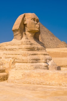 Le grand sphinx de gizeh et en arrière-plan les pyramides de gizeh, le plus ancien monument funéraire du monde. dans la ville du caire, egypte. photo verticale