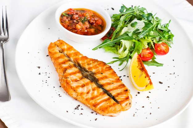 Le grand steak de saumon poisson rouge sur le grill avec citron, sauce avec légumes et légumes verts