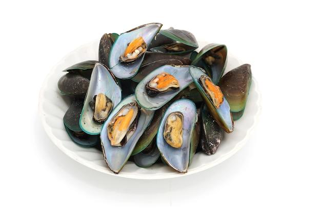 Un grand tas de moules cuites à la vapeur isolé sur fond blanc, fruits de mer populaires en thaïlande.