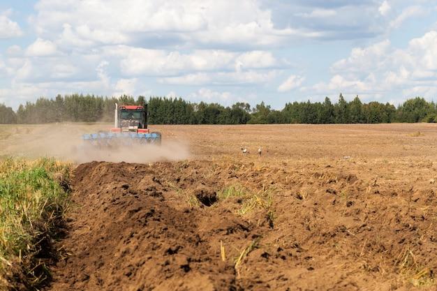 Grand tracteur avec une charrue laboure le sol sur le terrain après la récolte, pour semer une nouvelle récolte de plantes agricoles