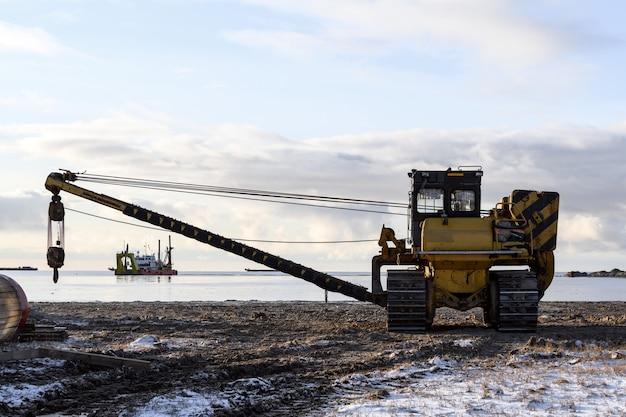 Grand tube sur chargeur. tracteur. travaux de construction marine en mer.
