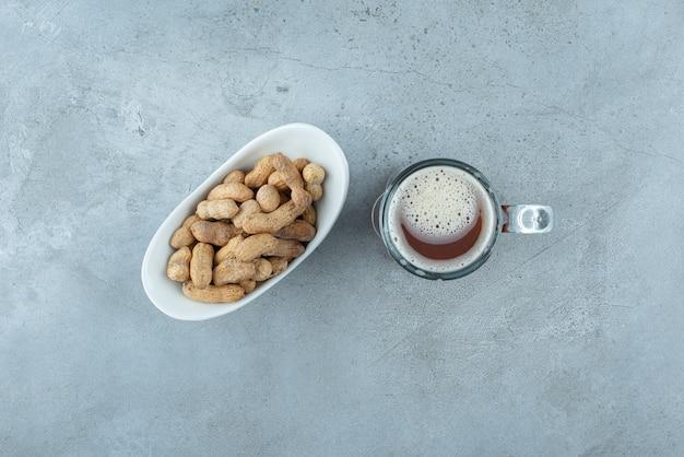 Un grand verre de bière avec une assiette blanche pleine de noix de cajou. photo de haute qualité