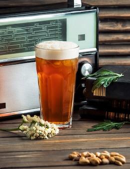 Un grand verre de bière et de cacahuètes salées.